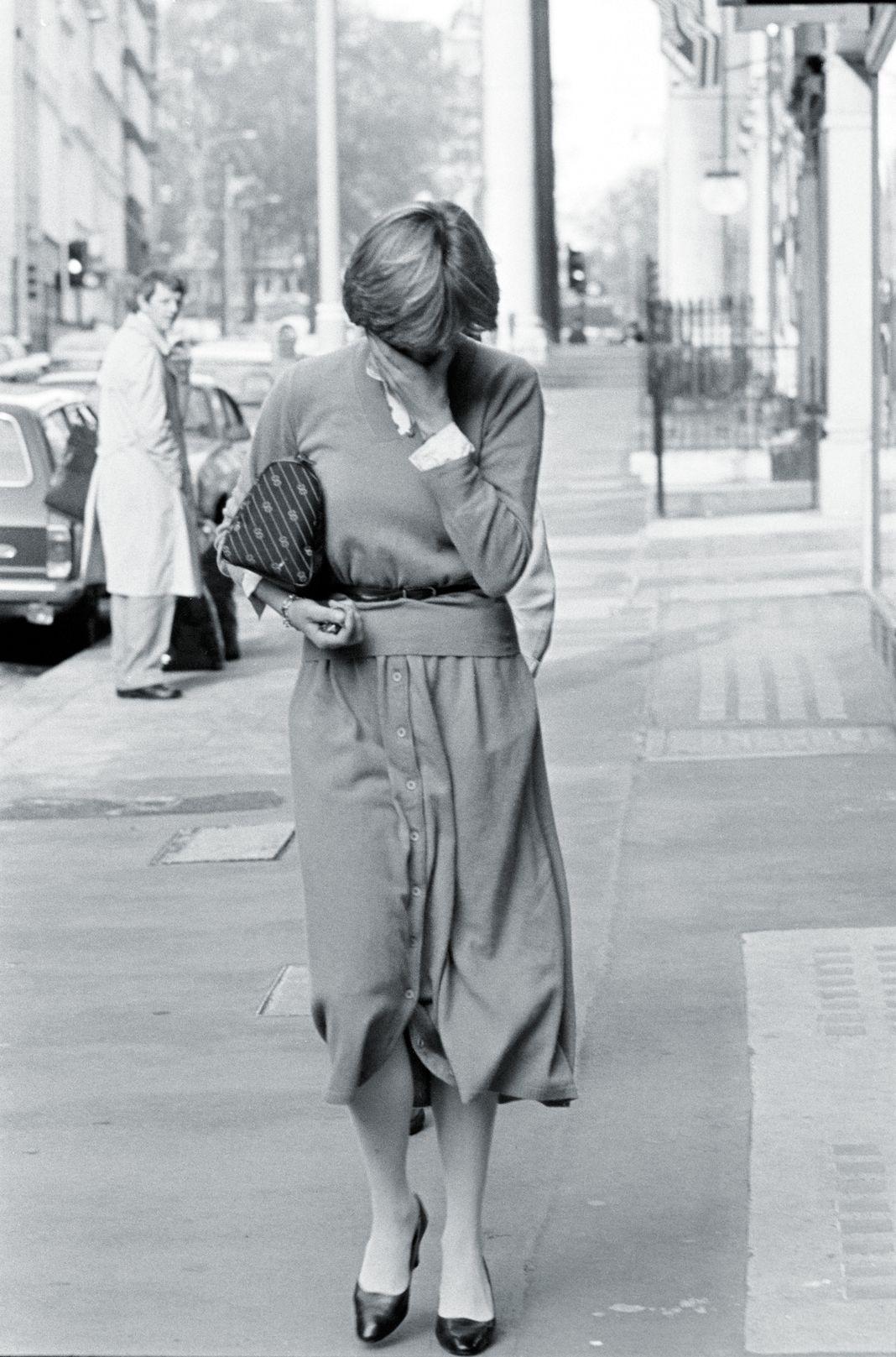 Леди Диана Спенсер закрывает лицо, идя по улице